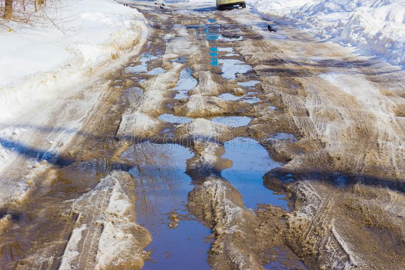 Holes and pothole on a rural road with snow stock photos