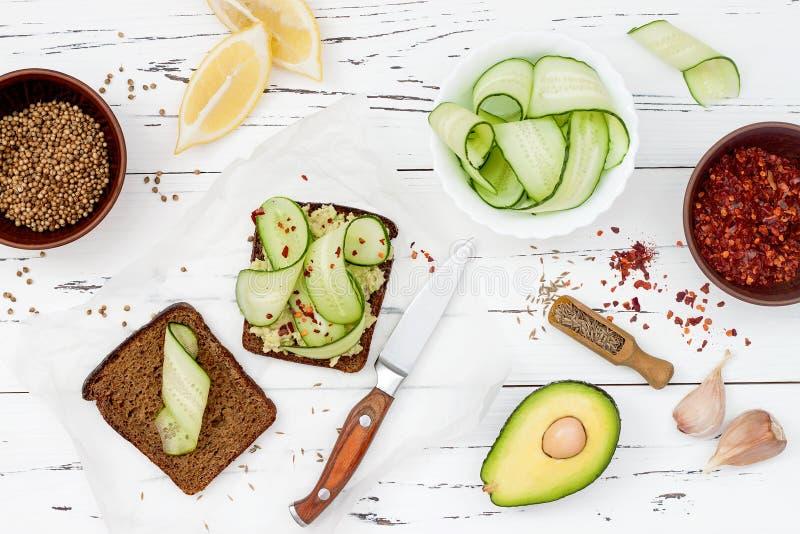 Holewheattoost met avocado guacamole en komkommerplakken Ontbijt met kruidige avocadosandwiches op geheel korrelbrood stock foto's
