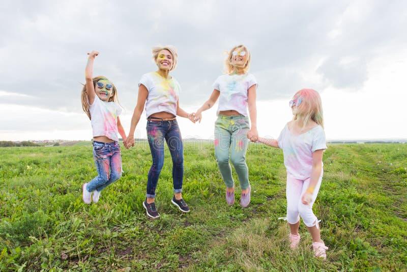 holi家庭、节日和假日概念-在油漆和女儿盖的画象母亲 免版税库存照片