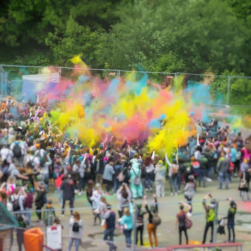 Holi,颜色节日,爱节日  模糊的无法认出的愉快的青年人,生动的尘土抽象人群  库存图片