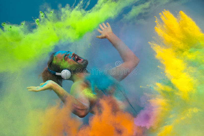 Holi celebration. Young guy listening music in headphones in the fog of colors during Holi celebration royalty free stock photography