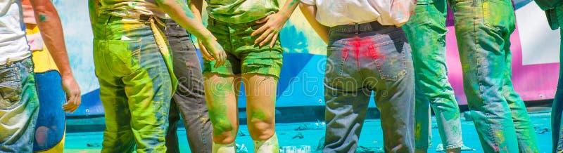 Holi di festa Un gruppo di giovani è spruzzato con le polveri luminose dei colori differenti fotografia stock