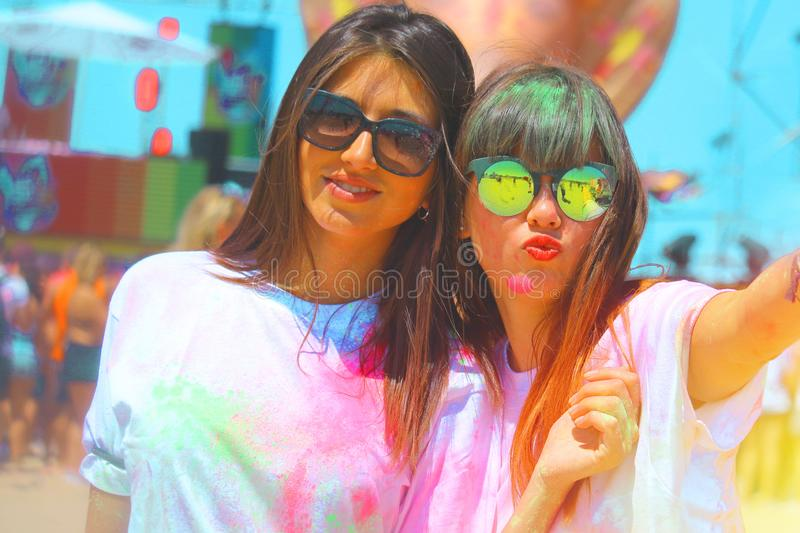 Best friends at holi festival two girls having fun colored with holi powder. royalty free stock images