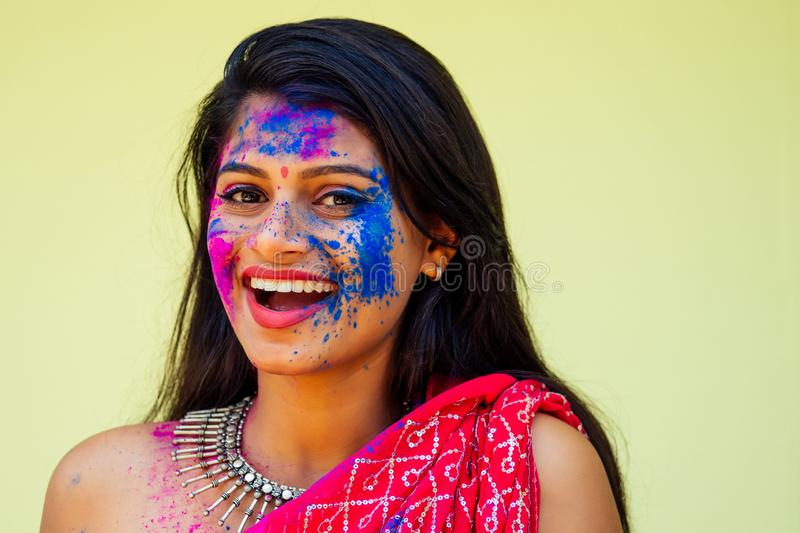 Holi Festival Of Colours. Portrait of happy indian girl in traditional hindu sari on holi color . india woman silver royalty free stock photo