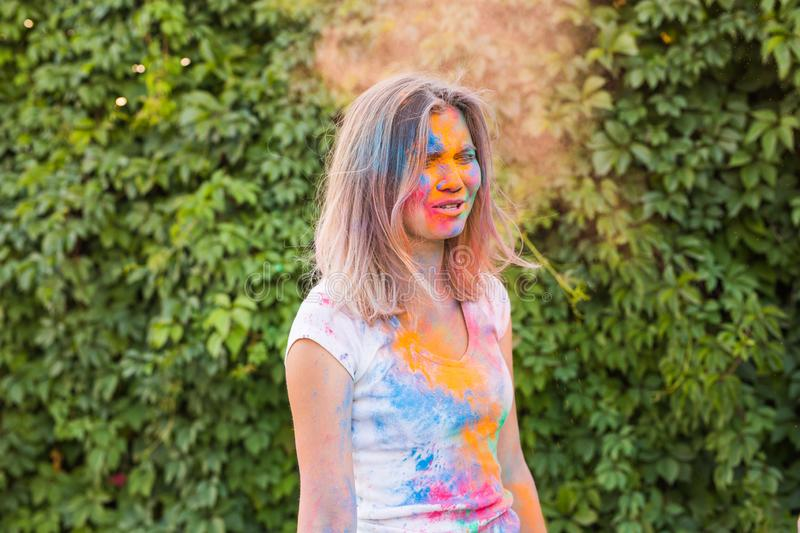 Holi festival, holidays and people concept - young woman having a fun at the festival of holi royalty free stock image