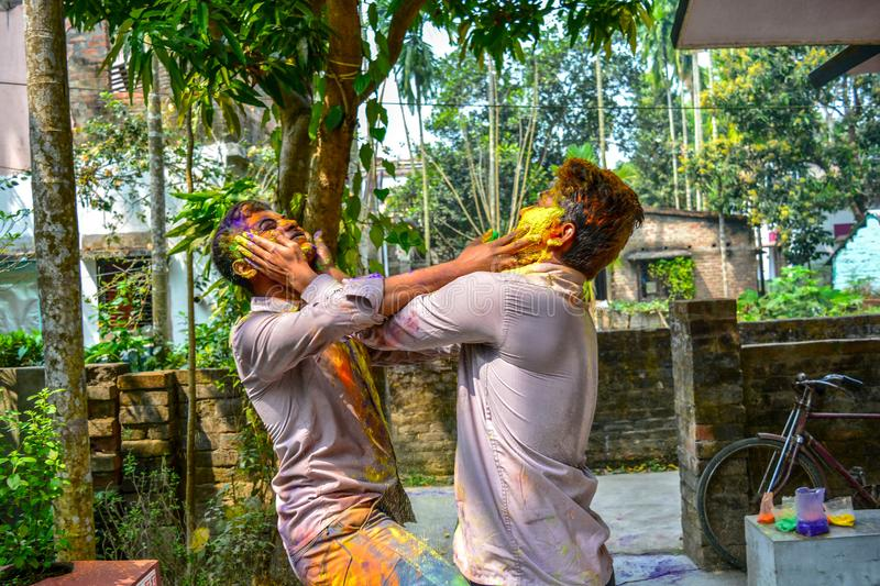During the Holi festival, two Indian friends are coloring each other. stock photo