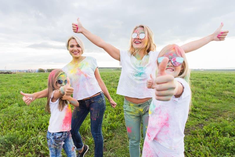 Holi festiwal, wakacje i szczęścia pojęcie, - młodzi wiek dojrzewania i kobiety w kolorach zabawę plenerową zdjęcia stock