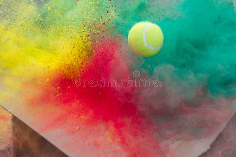 Holi múltiple colorea la explosión y una pelota de tenis fotografía de archivo libre de regalías