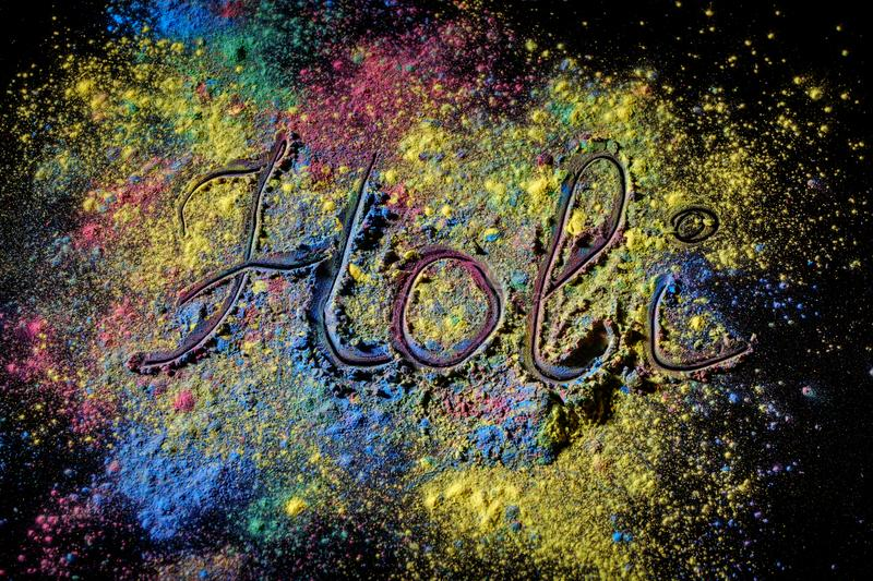 Holi paint festival background with lettering Holi . Color powder explosion on black. stock photography
