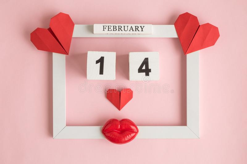 Holiday abstract made of picture frame, 14 of february wooden calendar and red paper hearts with plastic lips on rose stock photo