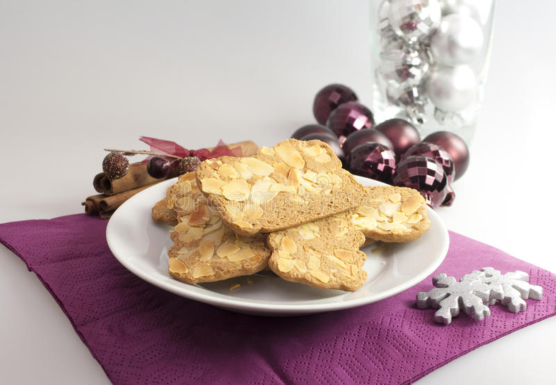 Holiday almond biscuits. A plate of hot, freshly baked almond biscuits garnished with Christmas or Holiday ornaments royalty free stock photos