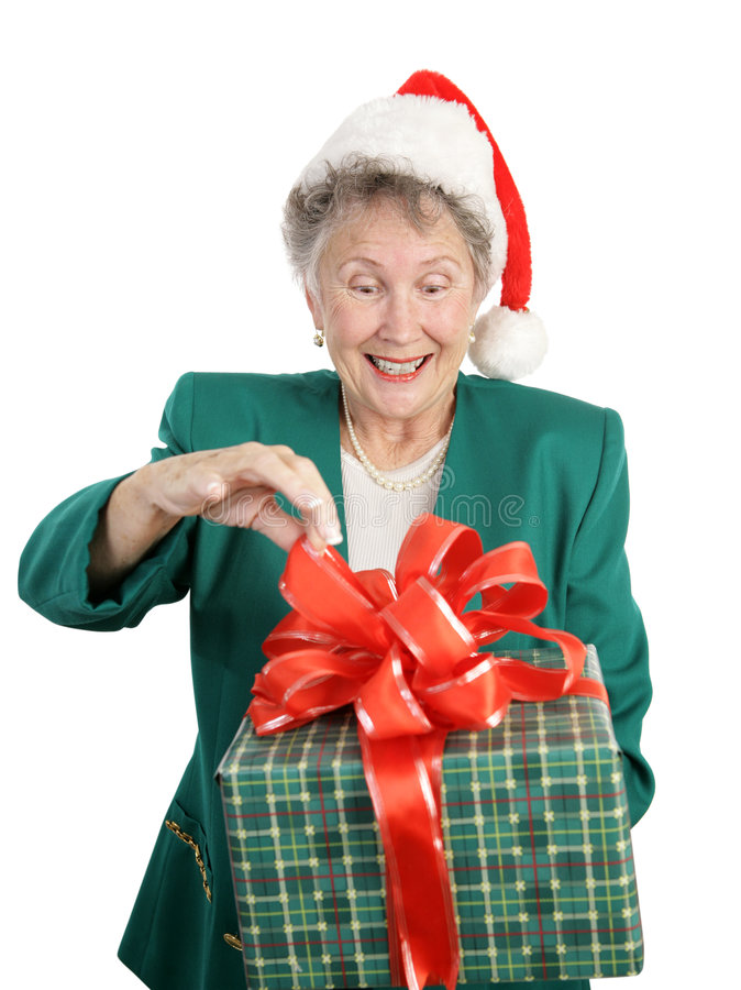 Holiday Anticipation. A senior woman anticipating opening a big Christmas gift. Isolated on white royalty free stock photos