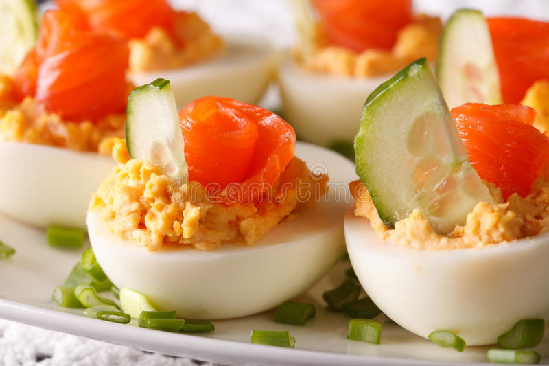 Holiday appetizer: Eggs stuffed with salmon macro. horizontal. Holiday appetizer: Eggs stuffed with salmon macro on a plate. horizontal royalty free stock image