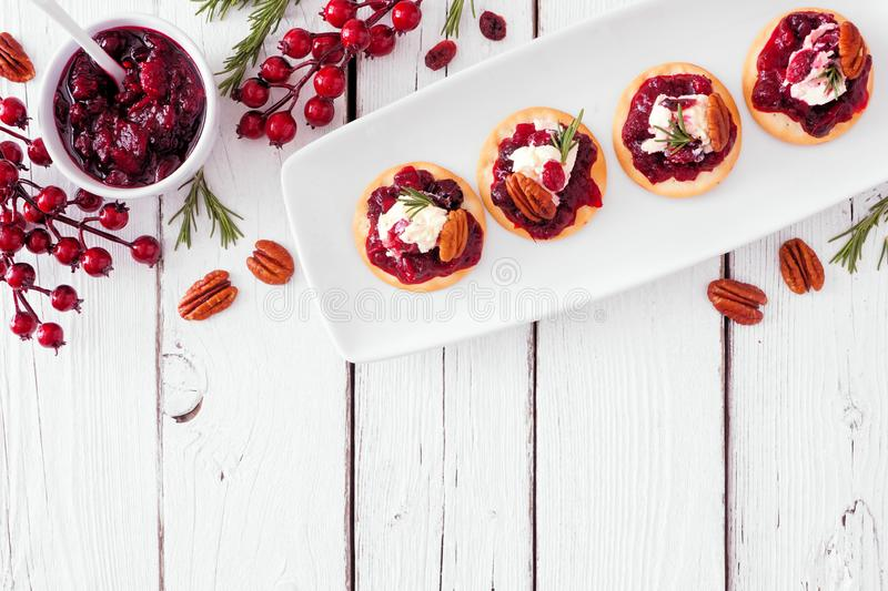 Holiday appetizers with cranberries, goat cheese and pecans, above view top border over a white wood background royalty free stock photography