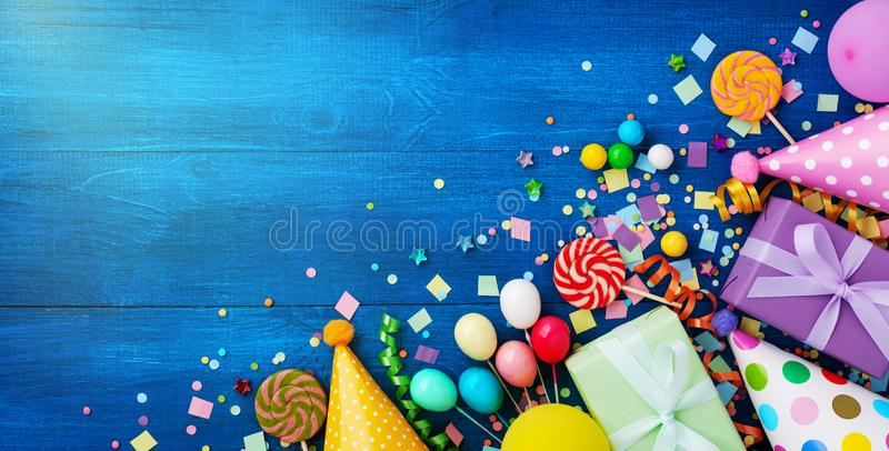Holiday background with balloons, gift boxes and confetti. Birthday and party supplies on blue table top view. Banner format royalty free stock photography