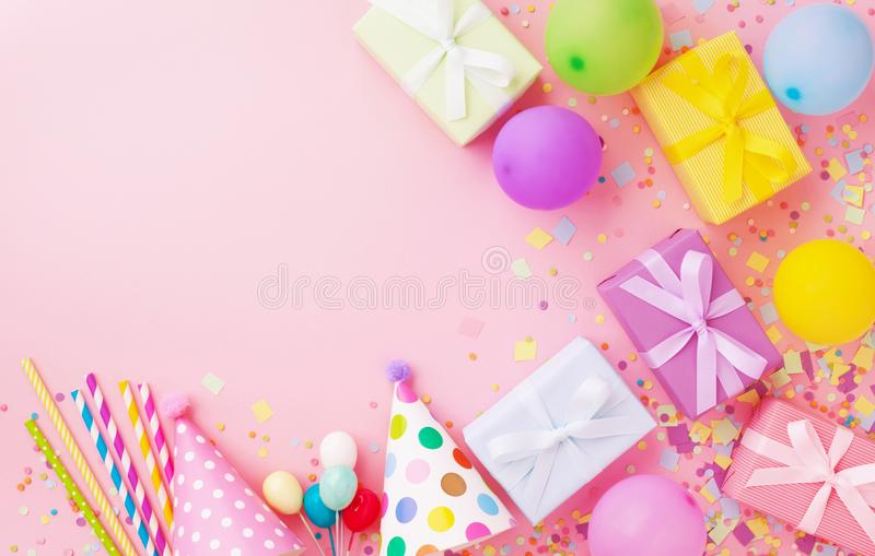 Holiday background with balloons, gift boxes and confetti. Birthday and party supplies on pink table top view royalty free stock photos