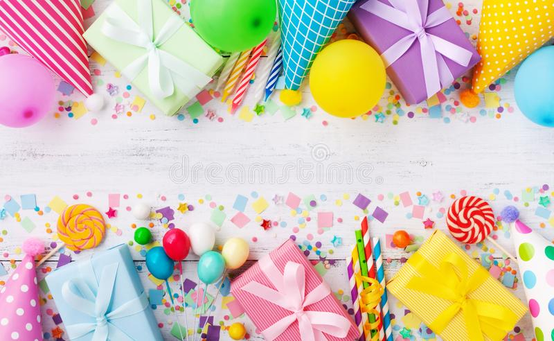 Holiday background with balloons, gift boxes and confetti. Birthday and party supplies on white table top view. Banner format.  stock image