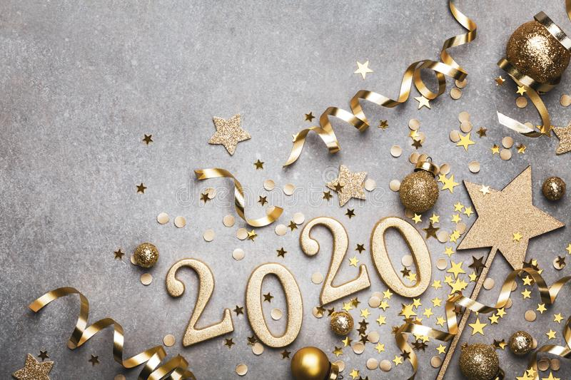 Holiday background with golden Christmas decorations and New year 2020 numbers and confetti stars top view. Holiday background with golden Christmas decorations stock image
