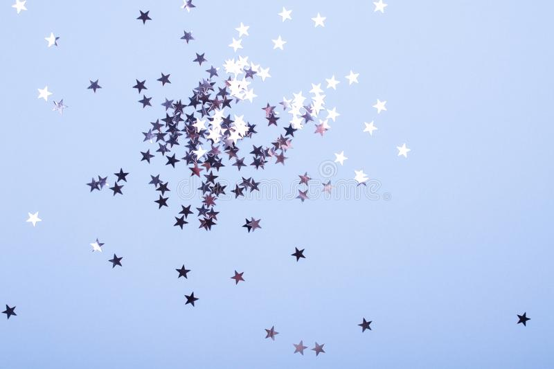 Holiday background. Group of little silver stars on blue pastel background. Top view. Copy space stock images