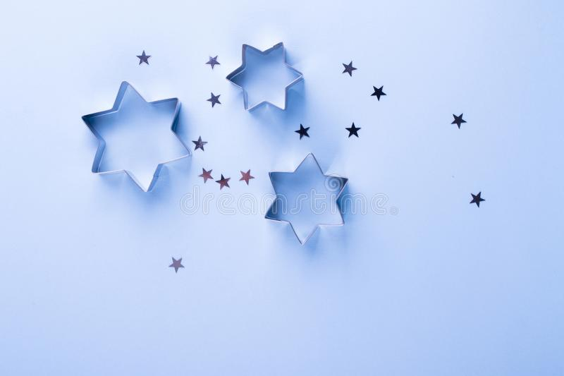 Holiday background. Group of little silver stars on blue pastel background. Top view. Copy space royalty free stock photography