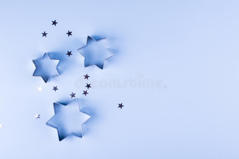 Holiday background. Group of little silver stars on blue pastel background. Top view. royalty free stock images