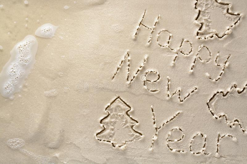 Holiday background - happy new year and Christmas tree, written on a tropical sandy beach royalty free stock photography