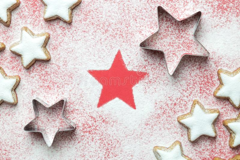 Flat lay of christmas star cookies with cutters and sugar powder in form of snow on red background minimal creative concept stock images