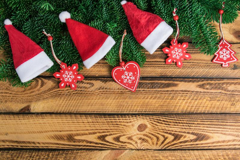 Christmas holiday background with Santa hats and traditional decoration on old wood. Holiday background with Santa hats and traditional Christmas decoration on royalty free stock photo