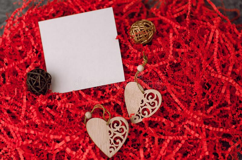 Holiday background for Valentine`s Day on a gray cement background with red chopped wrapping paper and hearts stock photography