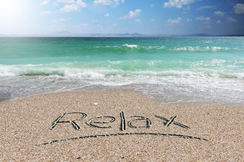 Holiday background or wallpaper with relax word handwritten on beach sand stock image