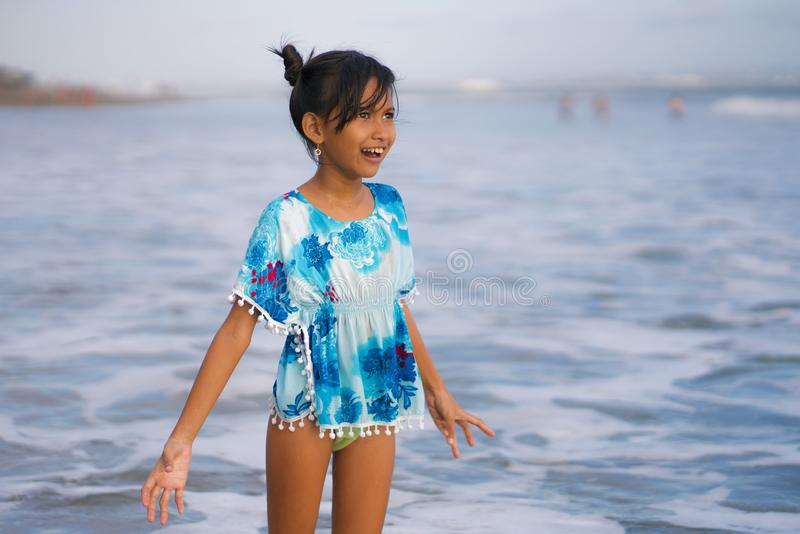 Beach lifestyle portrait of young beautiful and happy Asian child girl 8 or 9 years old with cute double buns hair style playing stock photo