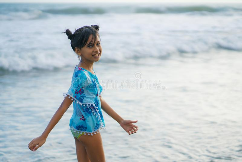 Beach lifestyle portrait of young beautiful and happy Asian child girl 8 or 9 years old with cute double buns hair style playing stock photography