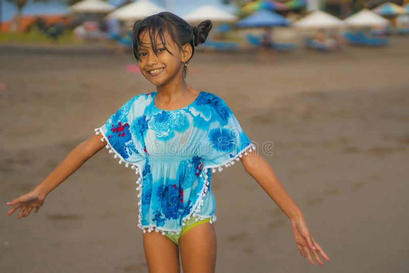 Beach lifestyle portrait of young beautiful and happy Asian child girl 8 or 9 years old with cute double buns hair style playing stock photos