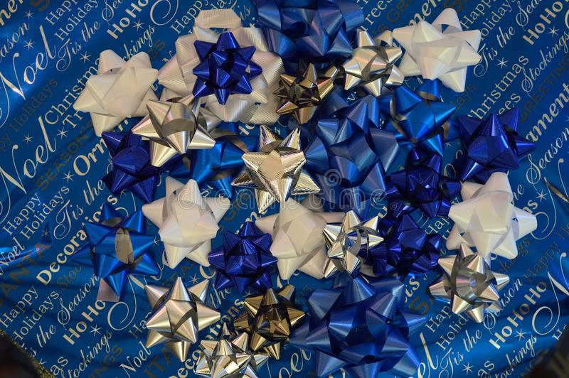 Holiday bows blue silver white theme horizontal rectangle. Holiday bows in blue, white, and silver, piled on wrapping paper in complimentary colors of blue royalty free stock photos