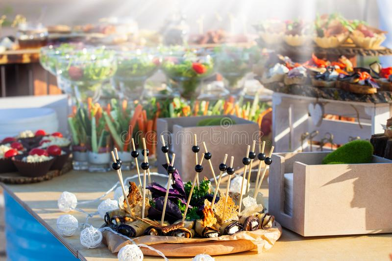 Holiday buffet table served by different canape, sandwiches, snacks ready for eating in catering restaurant at sunny day. Holiday buffet table served by stock image