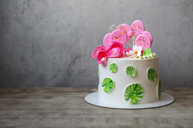 Holiday cake with monstera leaves design. Tropical birthday party inspiration. Tasty cake with wafer paper flowers and caramel candies stock image
