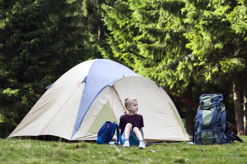 Holiday camping. Young boy sitting in front of a tent near backpacks taking rest after hiking in the forest shows something in th stock photography