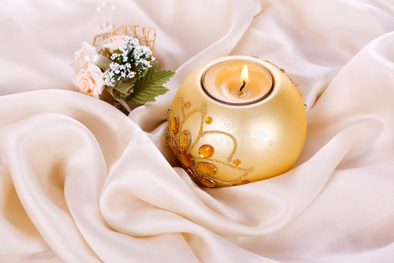 Holiday candle and flowers against stock photography