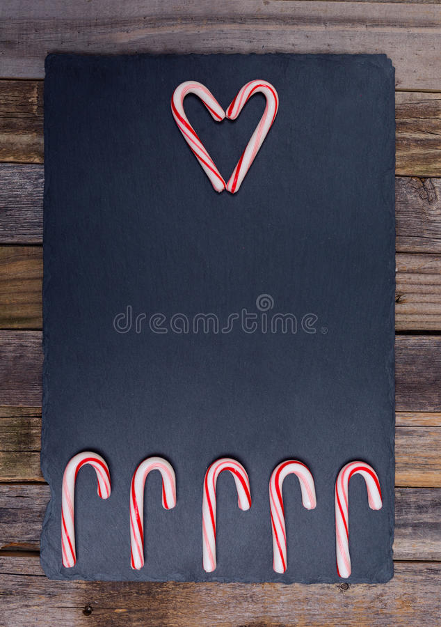 Holiday candy cane composition. With heart shape and fence of five canes on dark stone board and wooden background. Top view, flat lay stock images