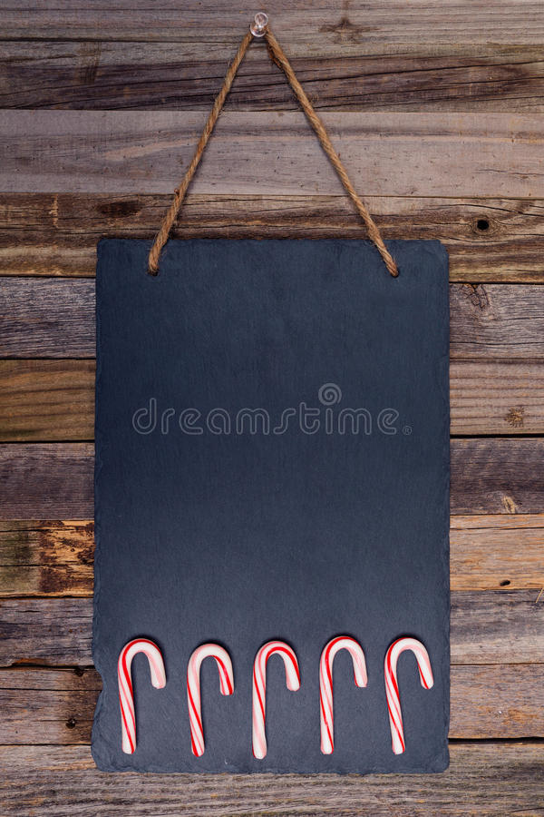 Holiday candy cane fence. On dark stone board pinned over wooden background. Top view, flat lay royalty free stock photography