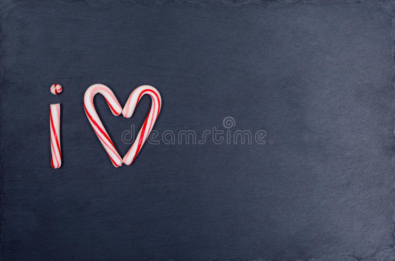Holiday candy cane heart shape abbreviated text I Love. On dark stone board background. Top view, flat lay stock photography