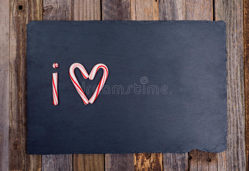 Holiday candy cane heart shape abbreviated text I Love. On dark stone board over wooden background. Top view, flat lay stock images
