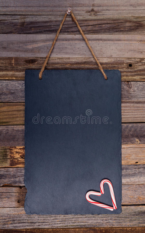 Holiday candy cane heart shape. On dark stone board pinned over wooden background. Top view, flat lay stock photography