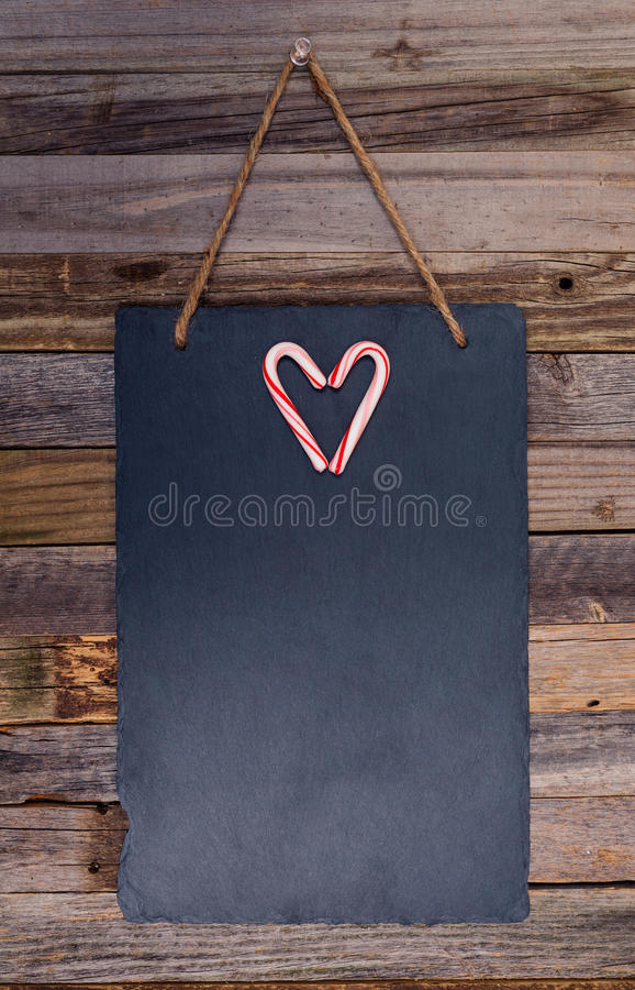 Holiday candy cane heart shape. On dark stone board pinned over wooden background. Top view, flat lay royalty free stock photos