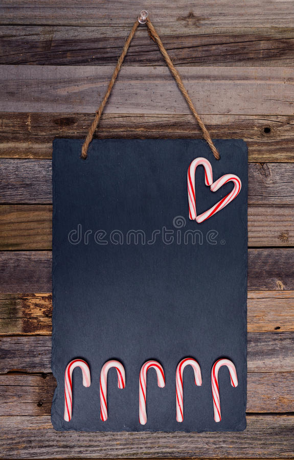 Holiday candy cane heart shape. And fence on dark stone board pinned over wooden background. Top view, flat lay royalty free stock photos