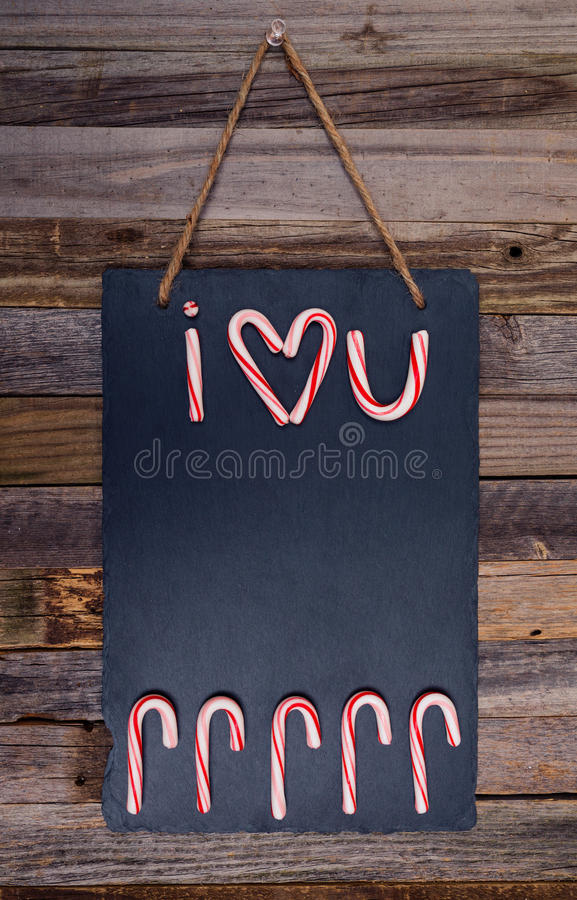 Holiday candy cane text I Love You. With heart shape on dark stone board pinned over wooden background. Top view, flat lay stock photography