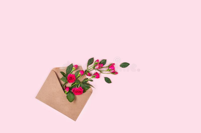 Holiday card with an envelope full of roses, top view. Greeting card. Blue background with envelope full of roses. Flat lay, top view, place for text stock image