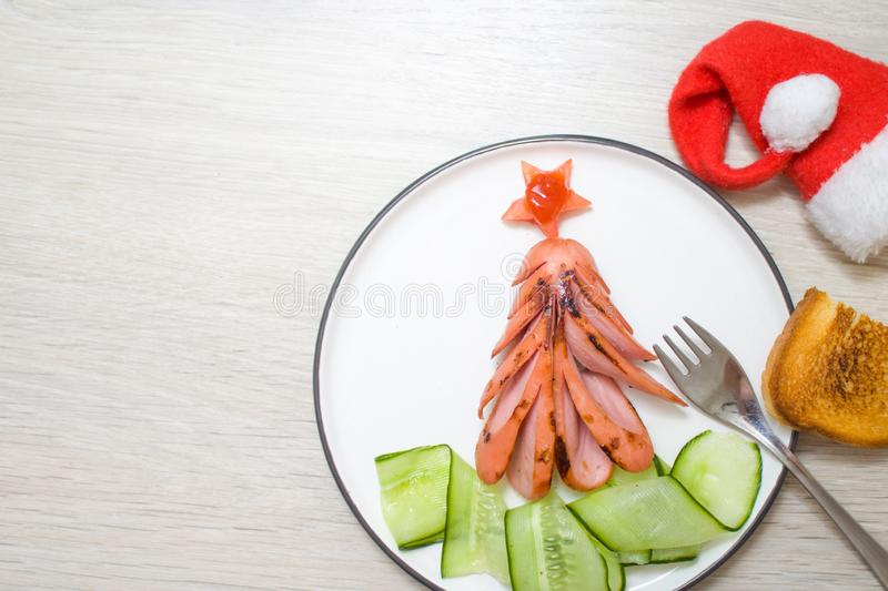 Holiday, celebration, food art concept. Funny edible Christmas tree made from fried grilled sausages, Breakfast idea for kids. New stock photos