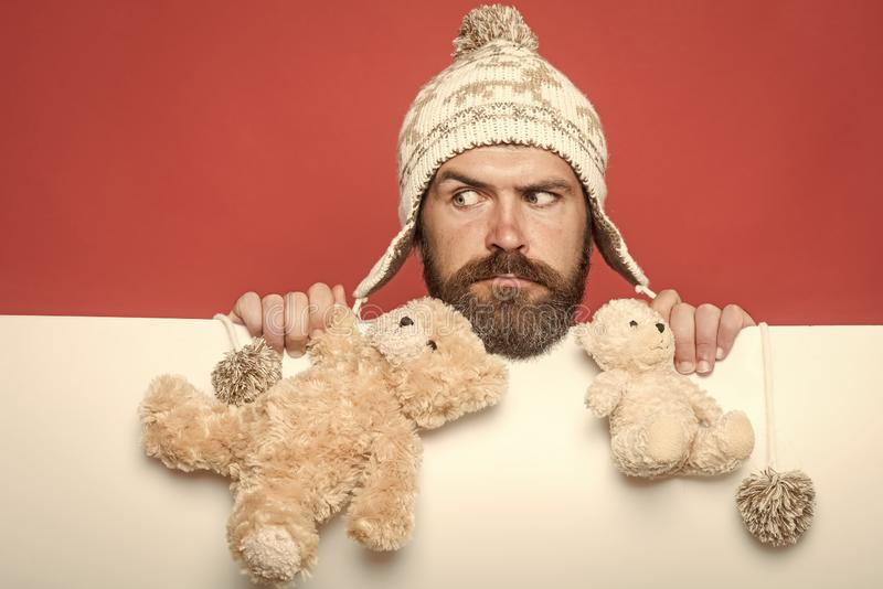 Holiday celebration and party. Christmas and birthday. Guy with serious face in winter hat. Hipster with toy on red. White background. Man with long beard hold stock photo