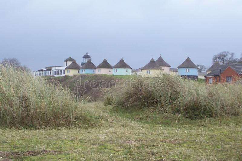 Holiday Chalets. At Horsey in Norfolk, England. The top of the lighthouse can be seen on the left royalty free stock image